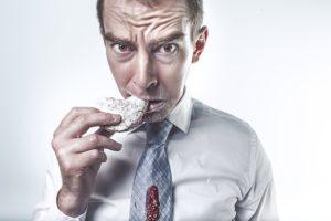 Stressed man eating cookie